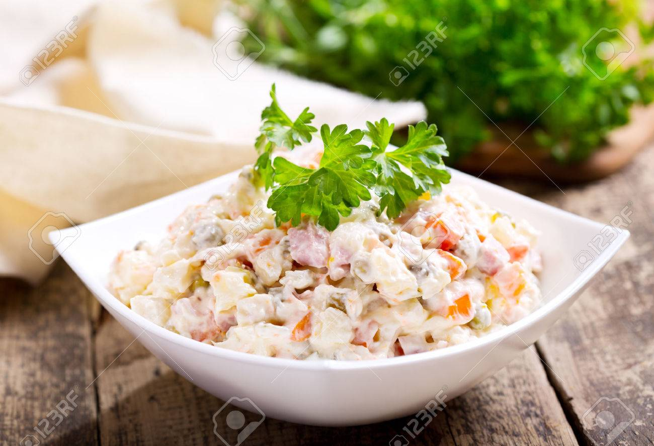 bowl of traditional russian salad on wooden table - 46521150