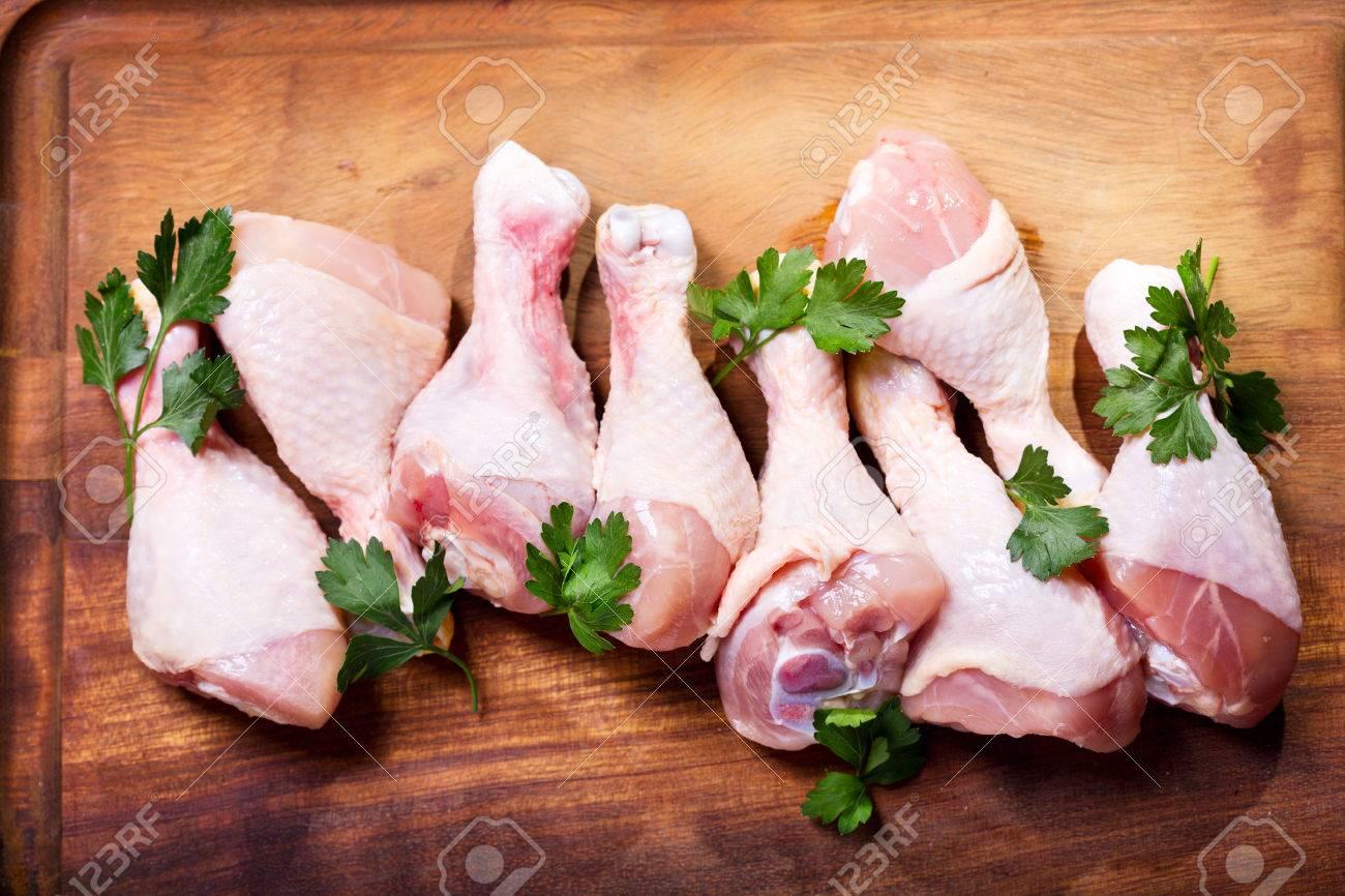raw chicken legs on wooden board - 49201060