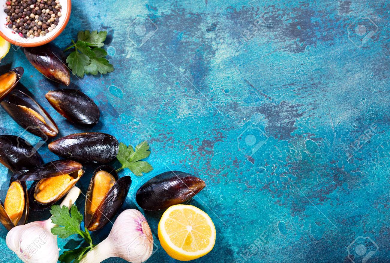 mussels with parsley and lemon on old blue background, top view - 55239622