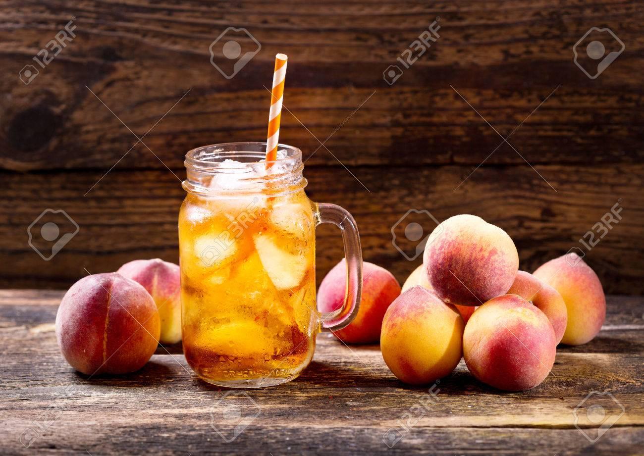 jar of peach iced tea with fresh fruit - 58134214