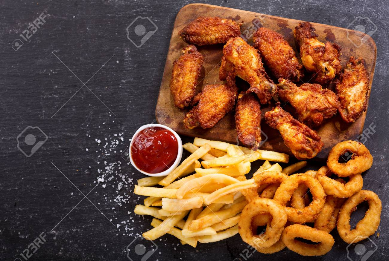 fast food products : onion rings, french fries and fried chicken on dark table, top view - 73324121