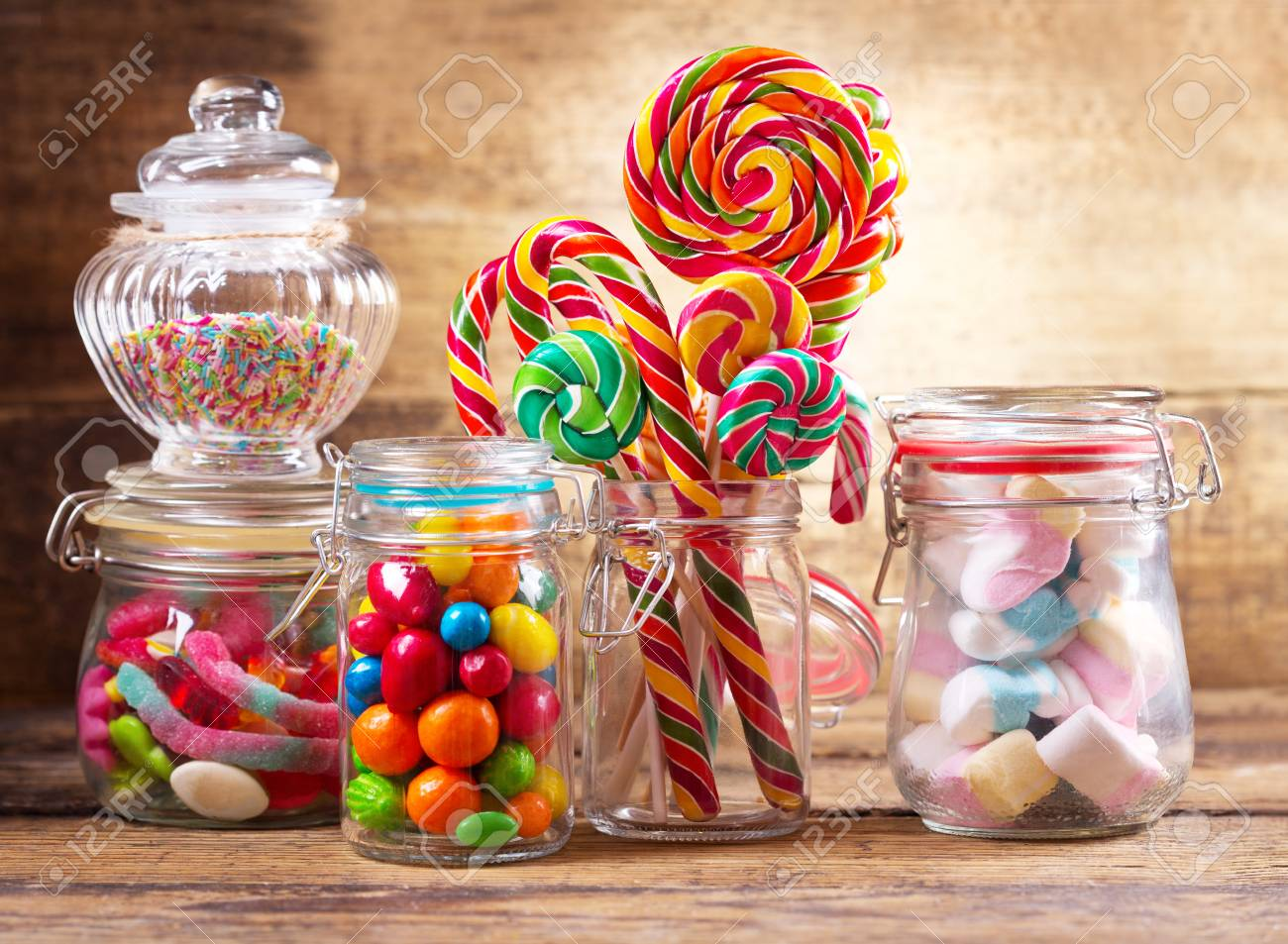 Colorful candies, lollipops and marshmallows in a glass jars on wooden table - 91470347