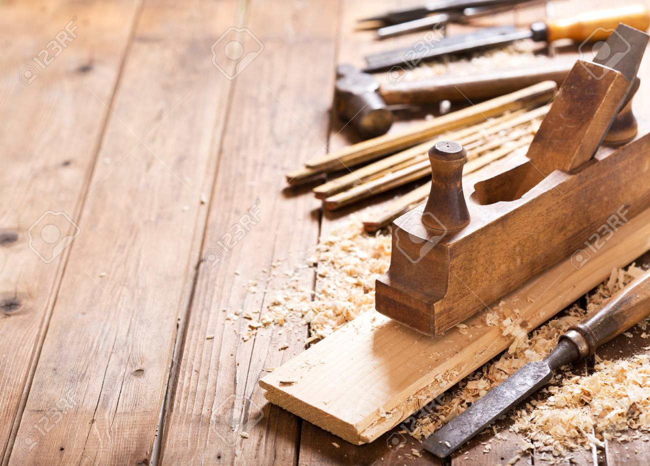 old tools: wooden planer, hammer, chisel in a carpentry workshop on wooden table - 101478122