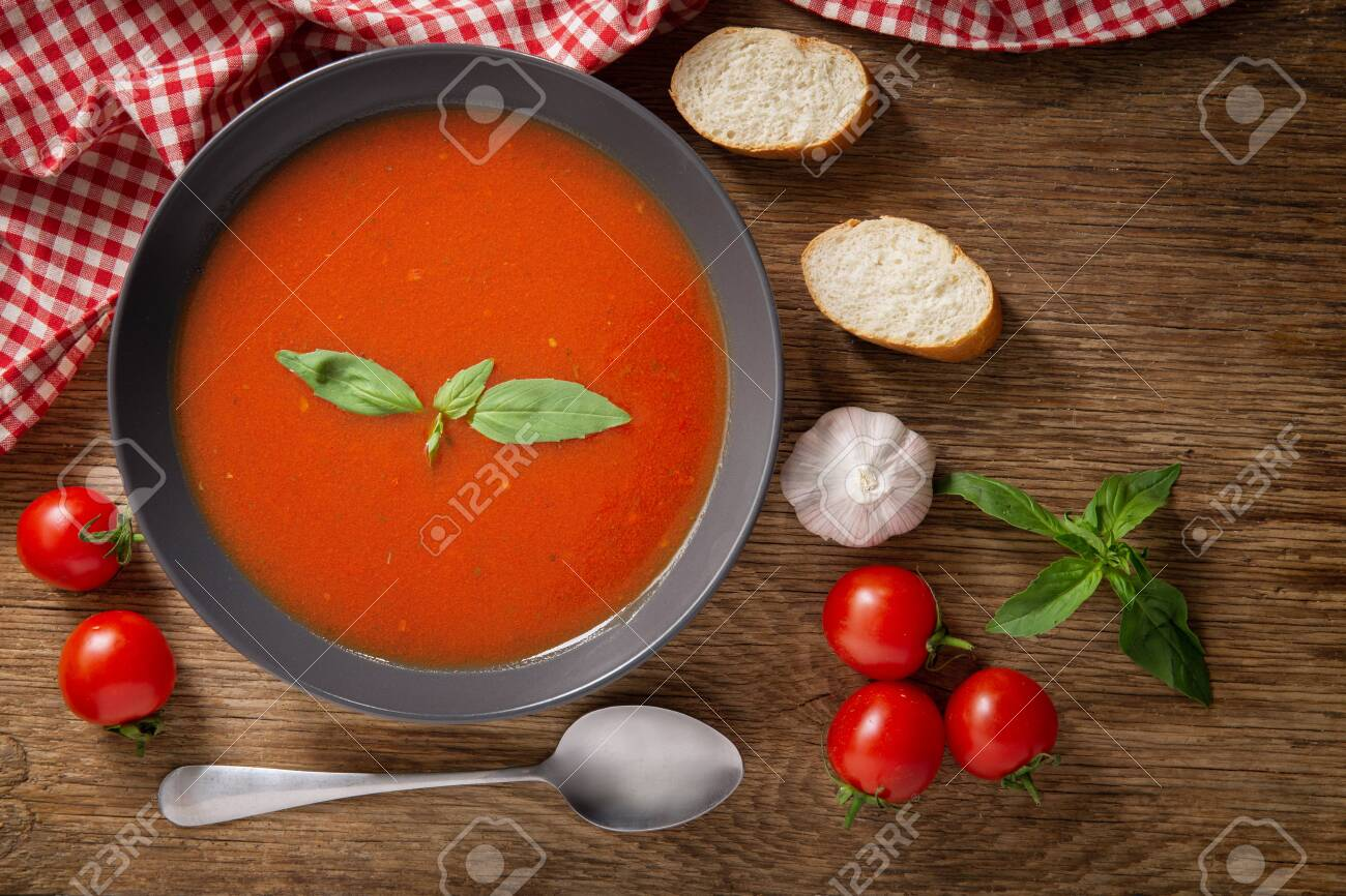 A bowl of tomato soup with basil on wooden table, top view - 144992161