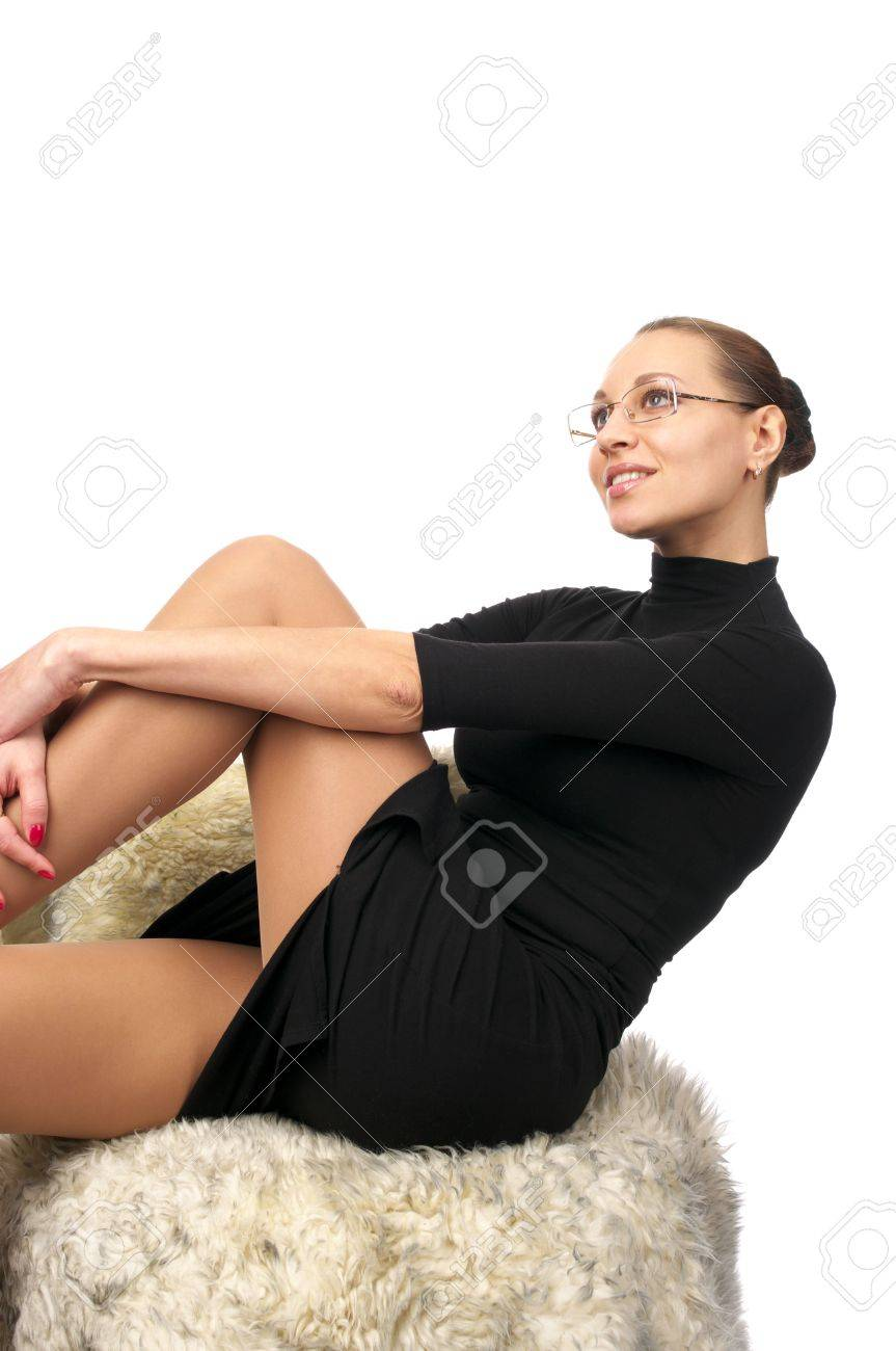 Beautiful sexy woman in black dress sitting in furry chair isolated over white Stock Photo - 6469811