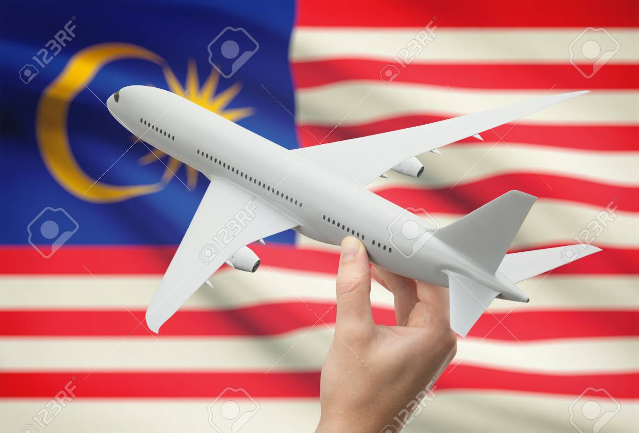 airplane in hand with national flag on background malaysia stock