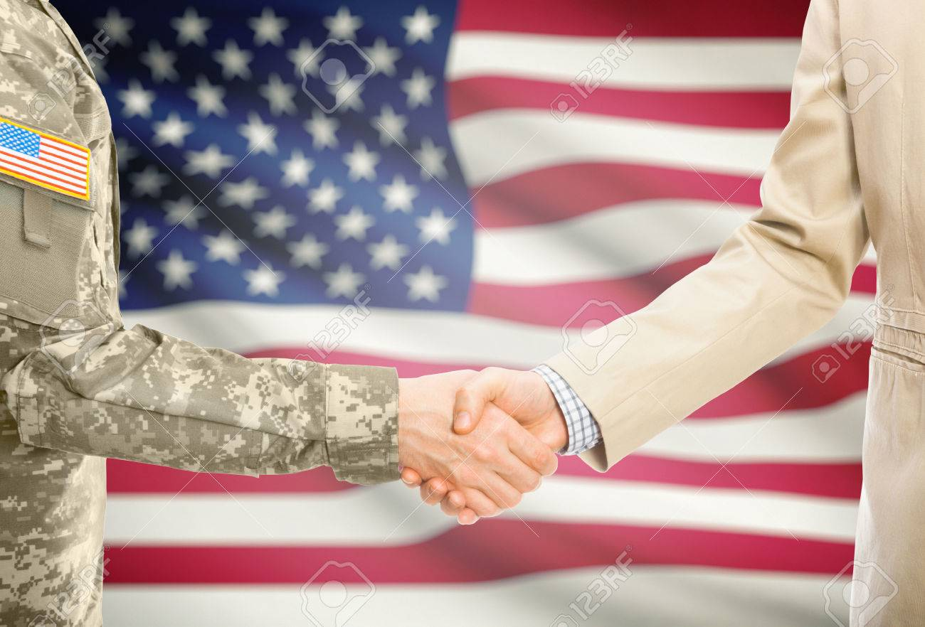 American soldier in uniform and civil man in suit shaking hands with national flag on background - United States - 51503994