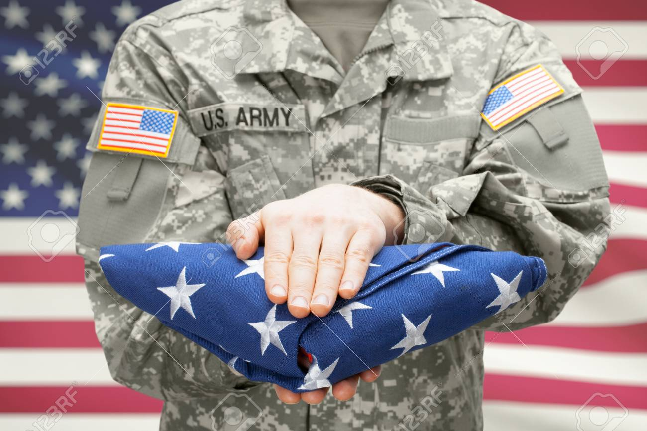 3a1a1281b960 Stock Photo - U.S. Army young soldier holding carefully folded USA flag  before his chest