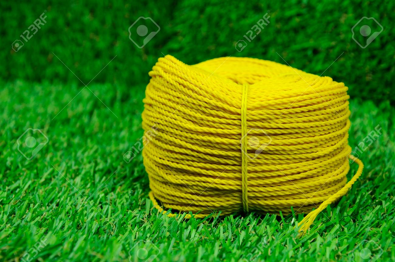 A roll of yellow nylon rope with on artificial grass background