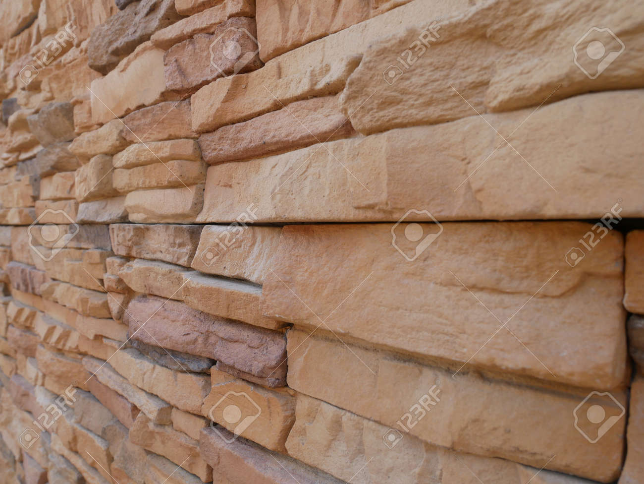 Slate brick in earth tone colour used as wall finishes. Installed overlap according to the method recommended by the manufacturer to get the maximum effect. - 164584797
