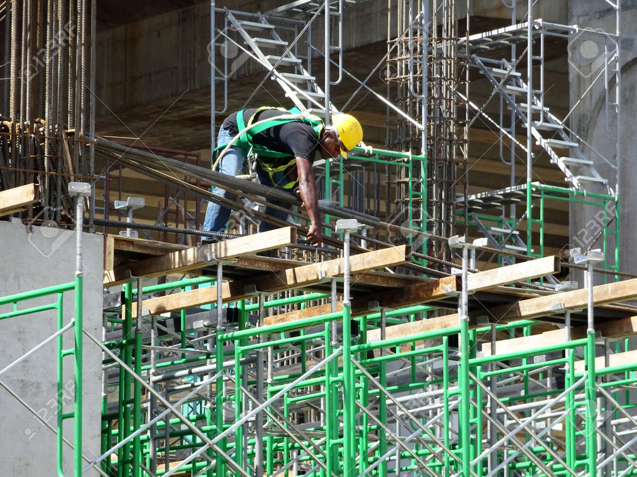 MALACCA, MALAYSIA -MARCH 2, 2020: Construction workers working at height install reinforcement bars at the construction site. They are supplied with harnesses and other safety equipment. - 165156374