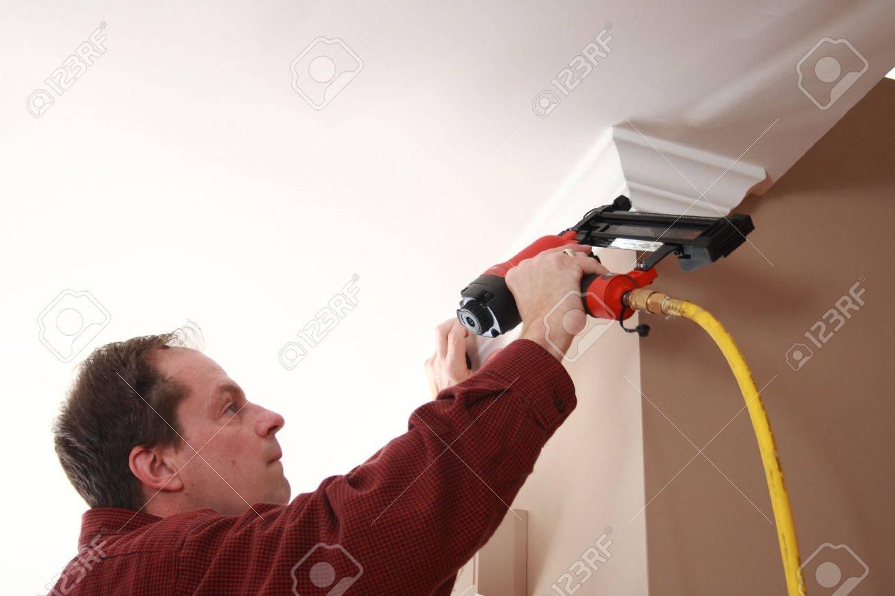 carpenter installing crown moulding - 13385395