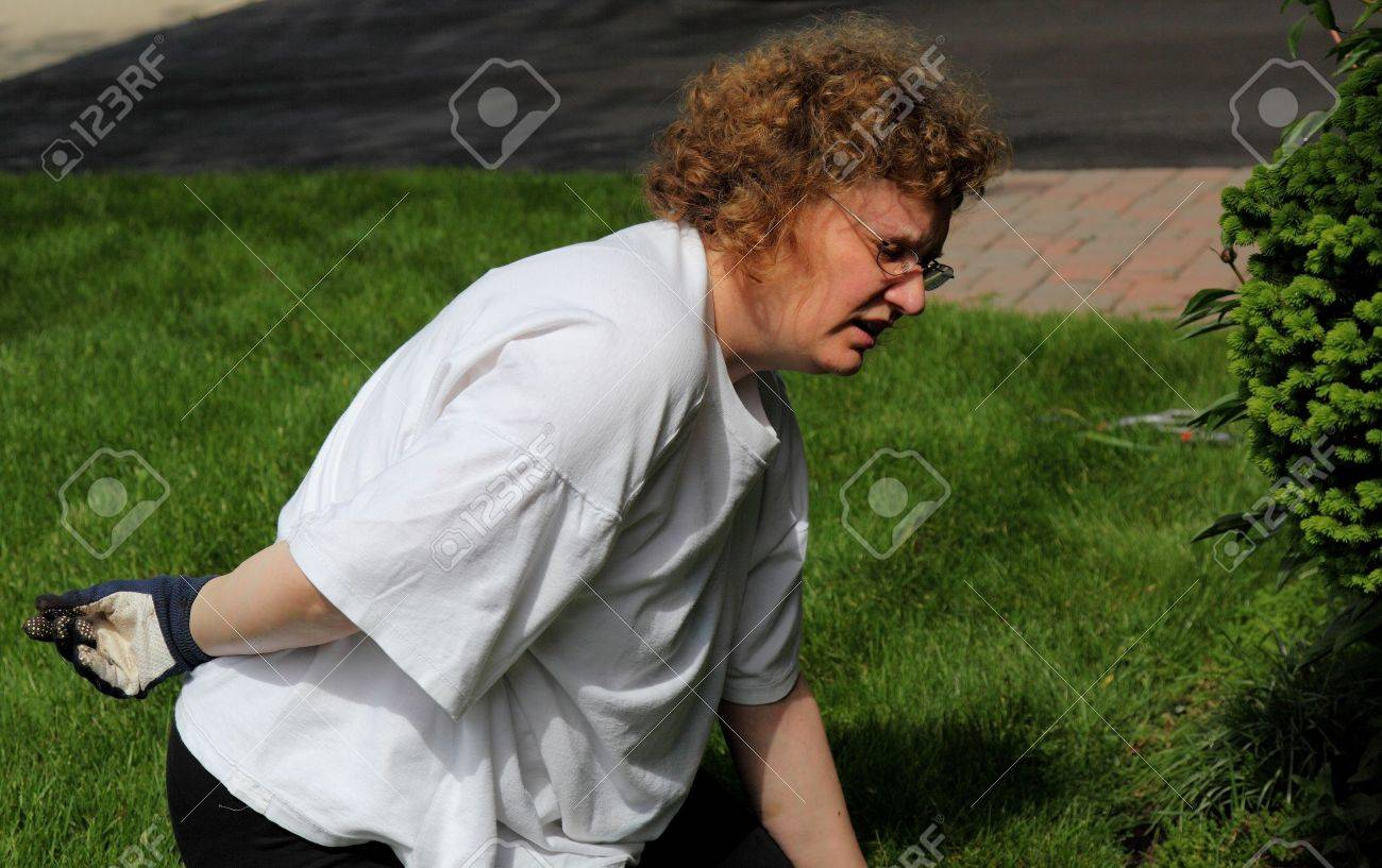 mature woman backache while gardening - 14282863