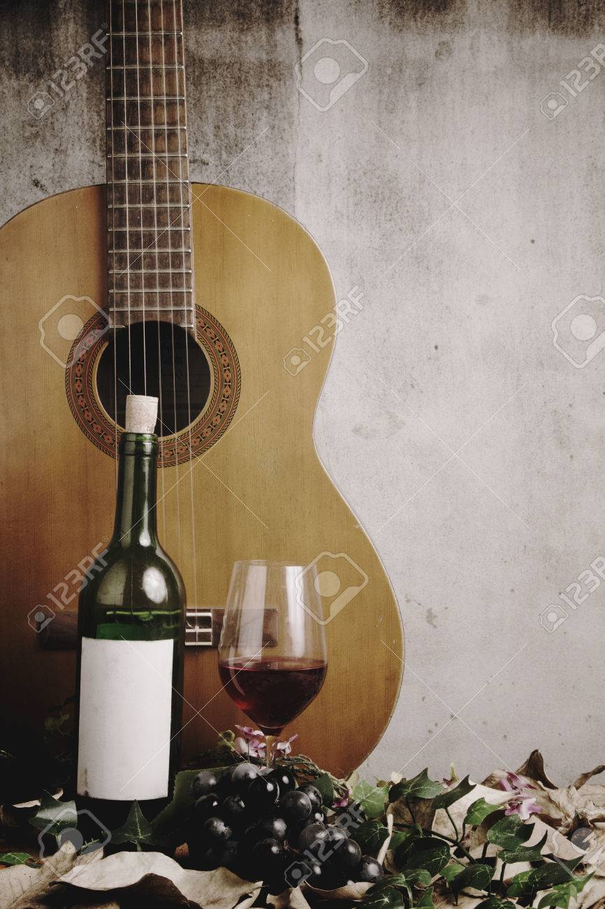 Still Life Of Red Wine Bottle And Glass With Acoustic Guitar Stock Photo