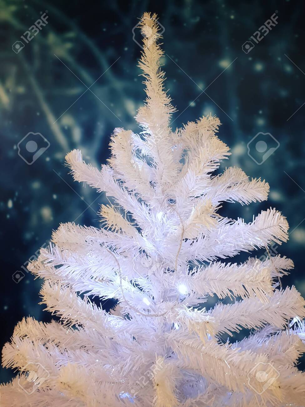 135408793 white christmas tree decorated with lights celebrate the festival with copy space garland background