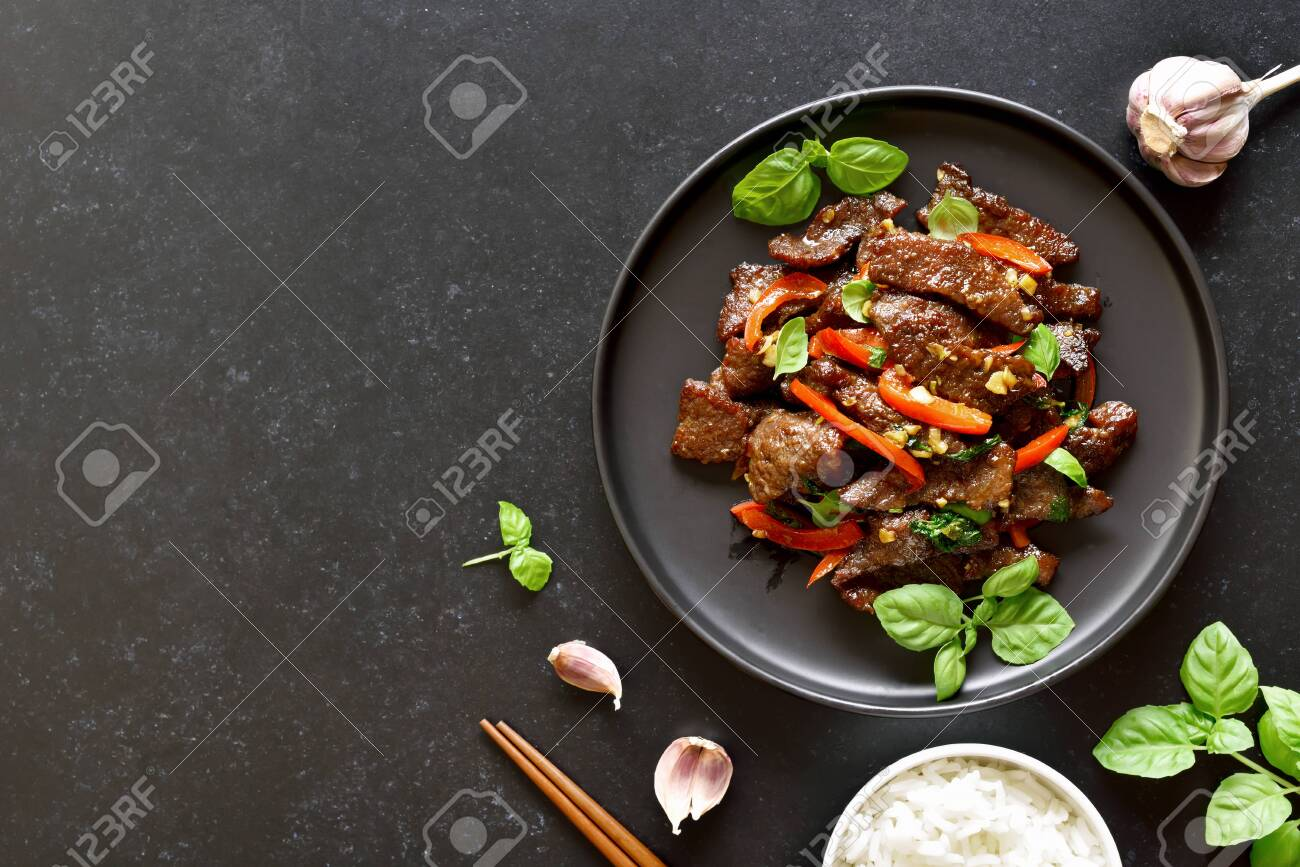 Thai beef stir-fry with pepper and basil on plate on a dark stone background with copy space. Top view, flat lay - 152490158