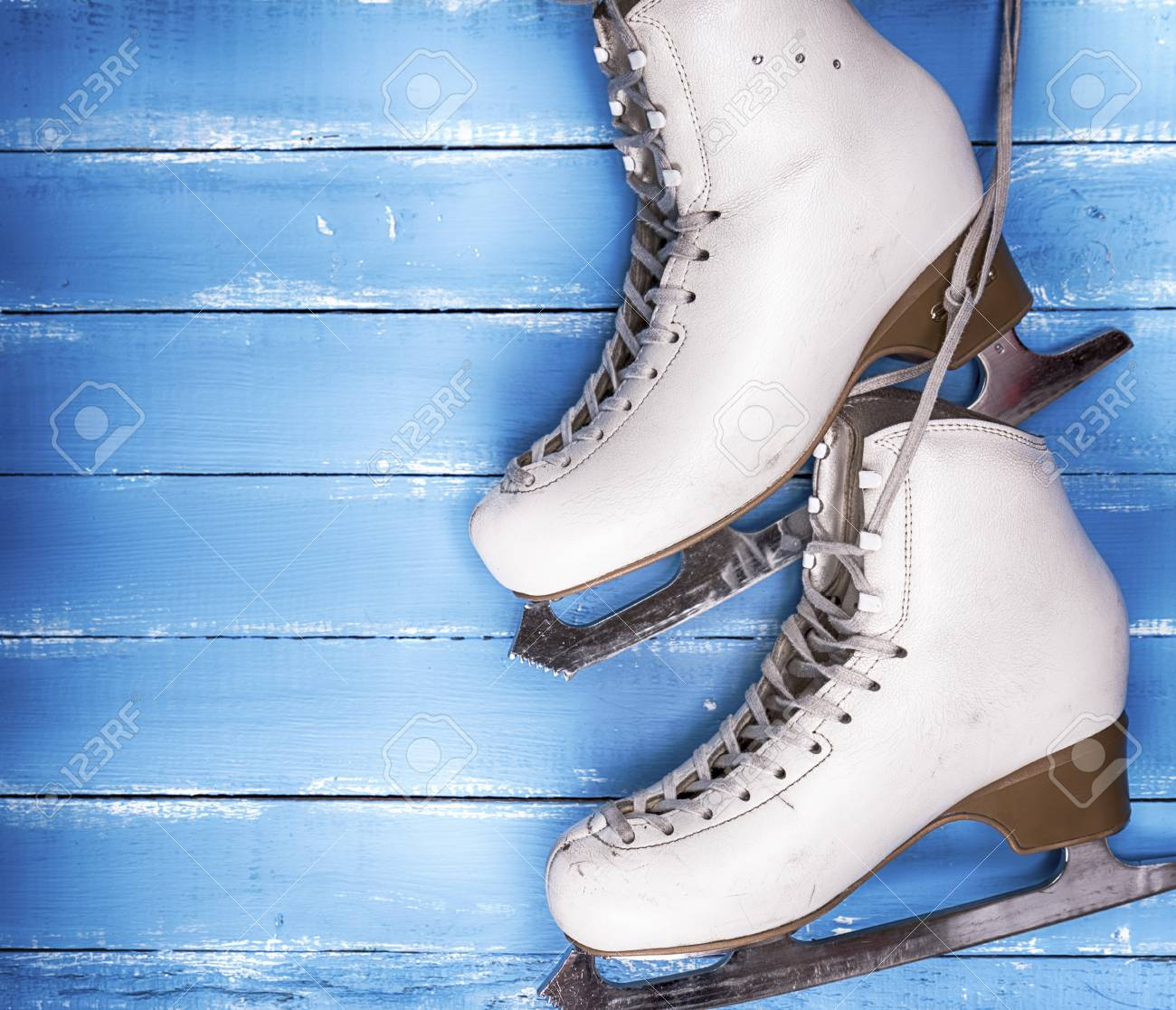 094989932ece8 a pair of worn white leather skates for figure skating on a blue..