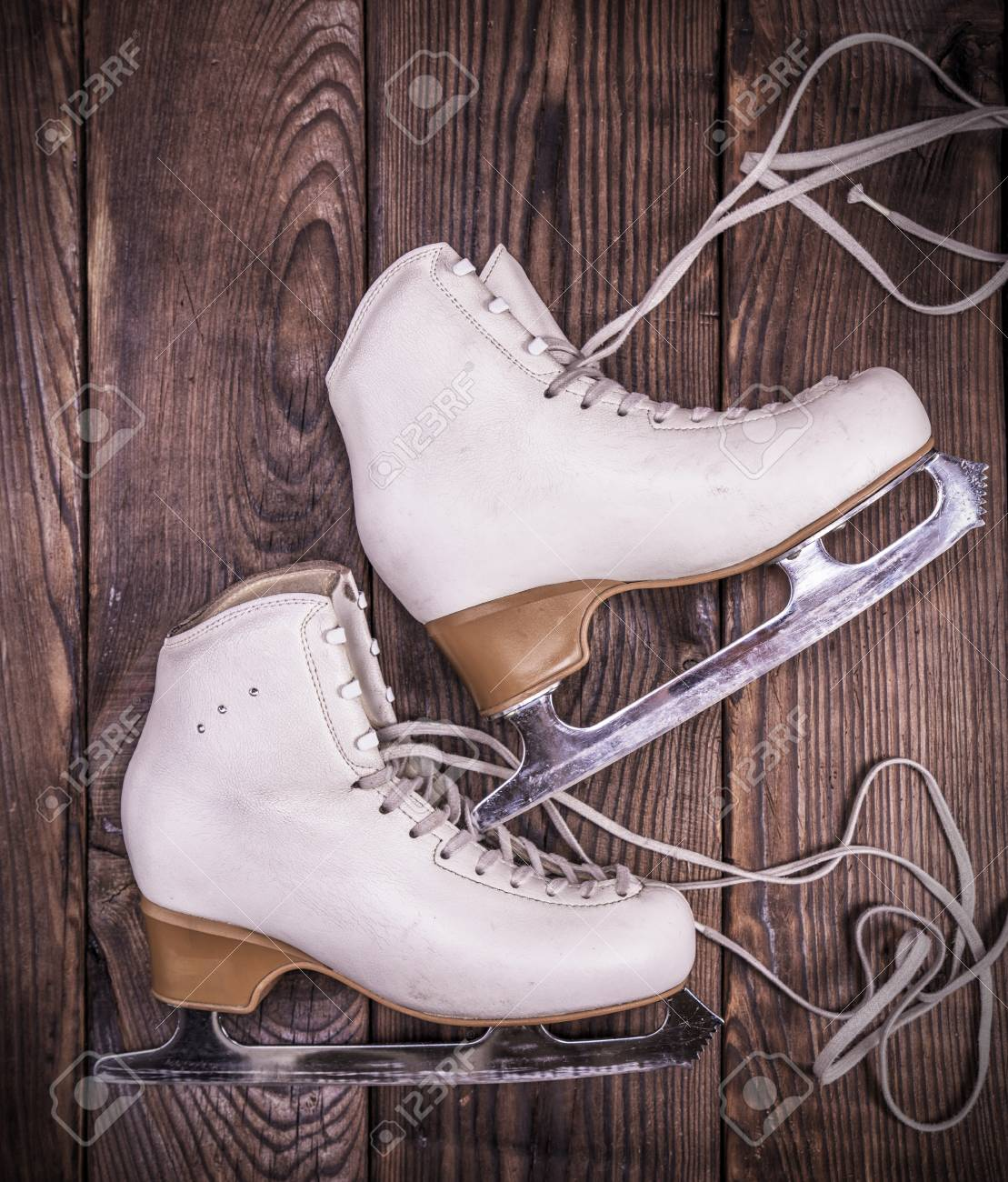 bbd74f315079b Female white leather skates for figure skating on a brown wooden..