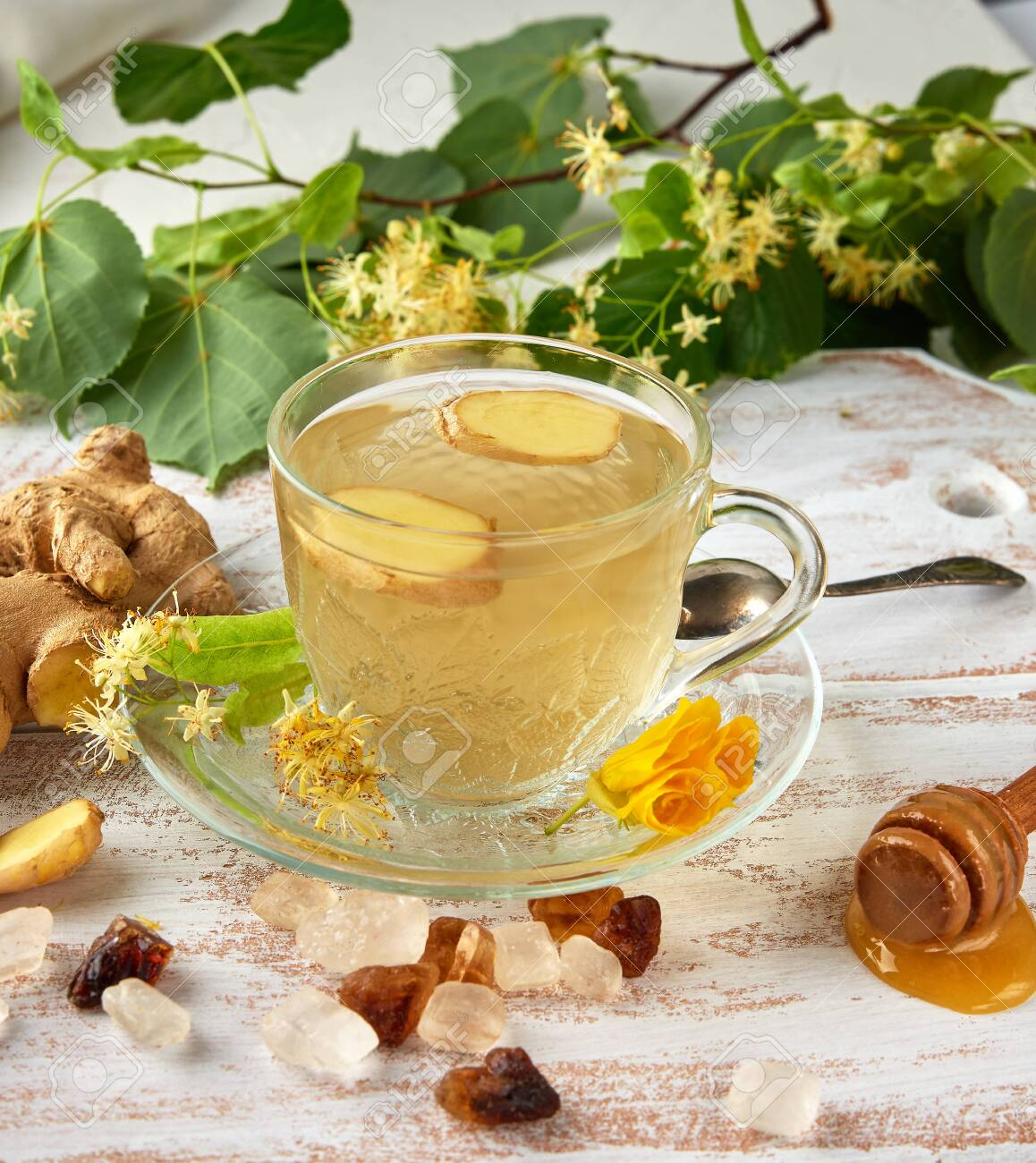 transparent cup with tea from ginger and linden on a white wooden board, top view - 128721362