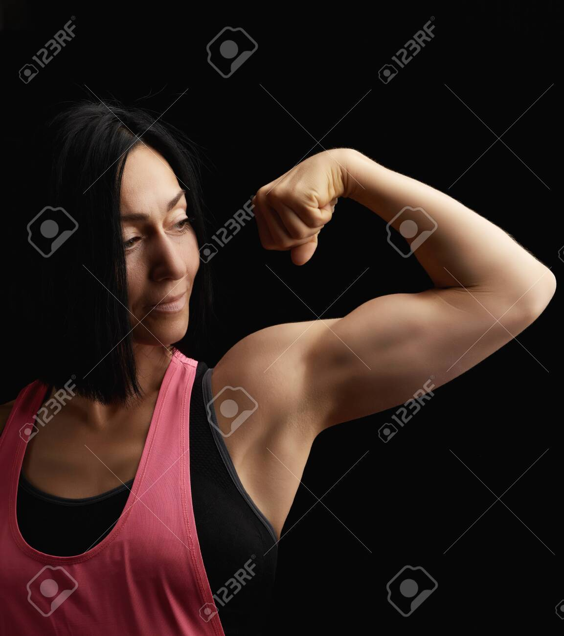 beautiful athletic girl raised and bent her arm demonstrating her biceps, athlete is standing on a dark background, wearing a black top - 134332696