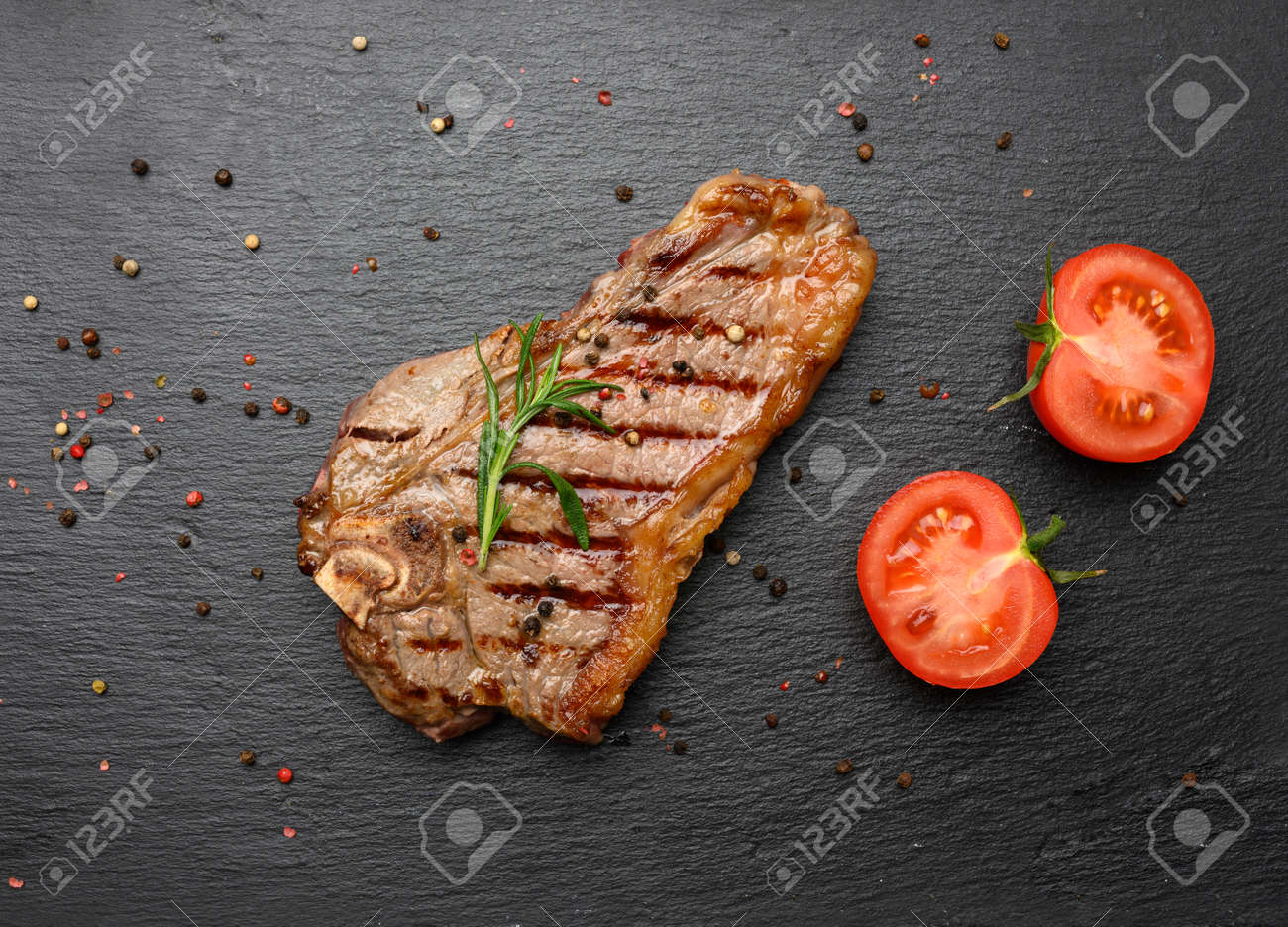 whole fried New York beef steak on a black board, striploin doneness rare, top view - 169040130