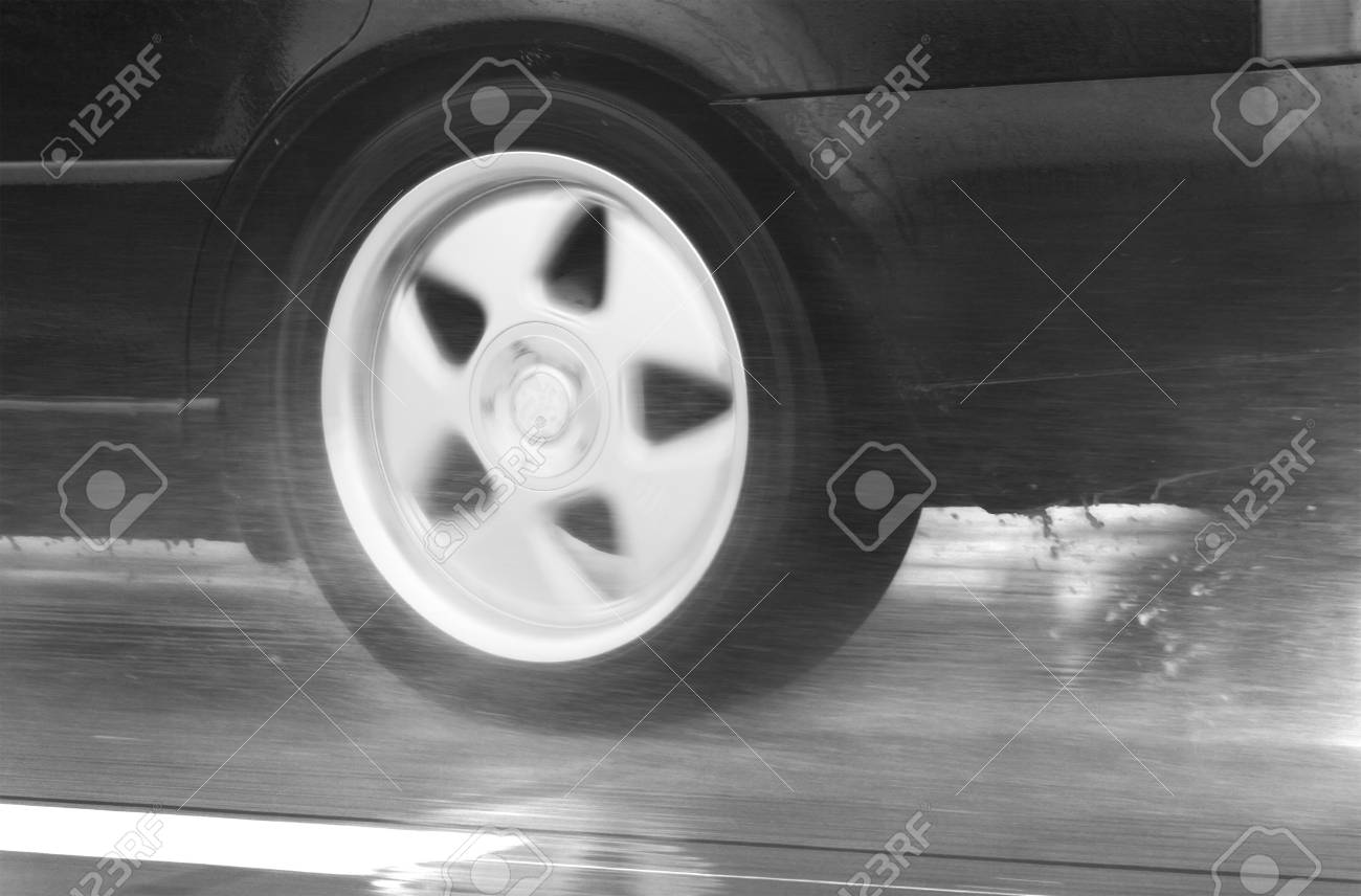 wheel of speeding sport car driving fast in a rainy day Stock Photo - 11042762