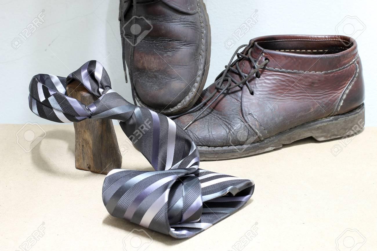 Set di accessori di moda uomo, stivali marroni e grigio e nero cravatta a strisce su fondo in legno. Buona festa del papà