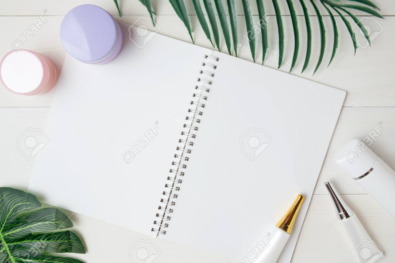 cosmetic and skin care product and notebook and leaves on table, beauty with treatment cream and moisturizing and notepad copy space on wooden desk, health and wellness concept, top view. - 121119406