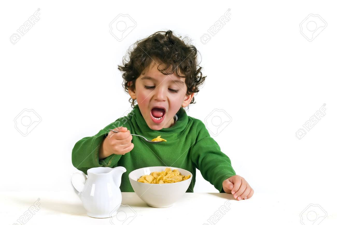 young boy eating cornflakes isolated on white Stock Photo - 2571954