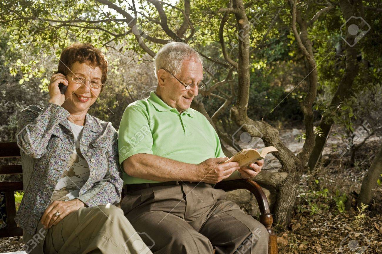 seniors couple sitting on a bench talking on the cell phone and reading in the park Stock Photo - 3527765