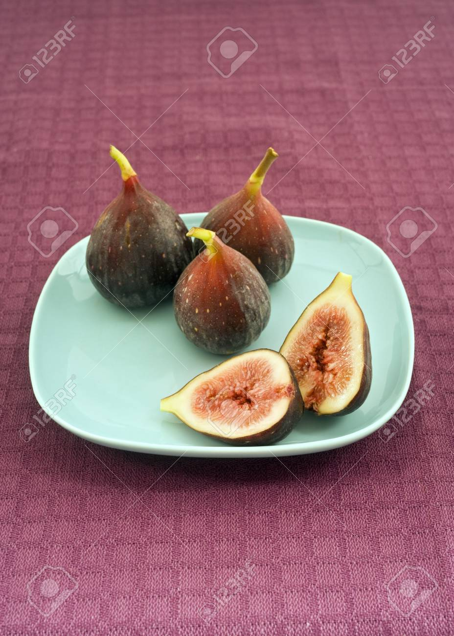 still life three whole figs and one sliced on blue plate Stock Photo - 3593726