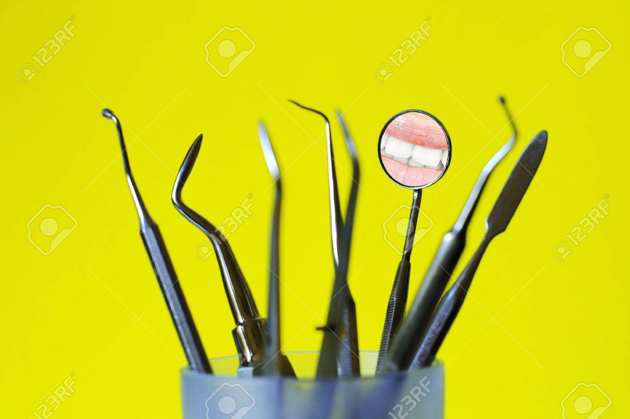 Angled mirror with smile reflection and dental tools in a glass , yellow background Stock Photo - 8573672