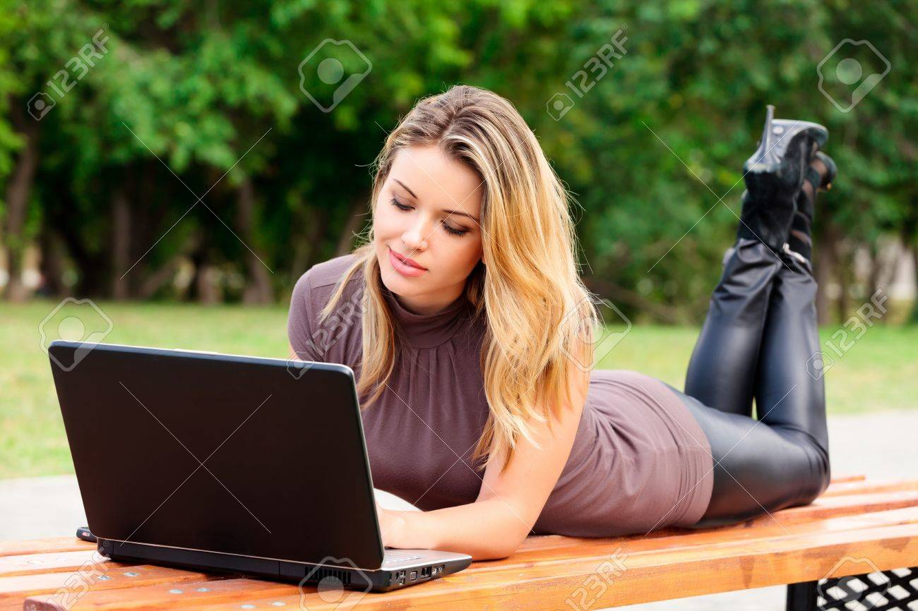 Young pretty woman with laptop lying on the bench in a park Stock Photo - 7363508