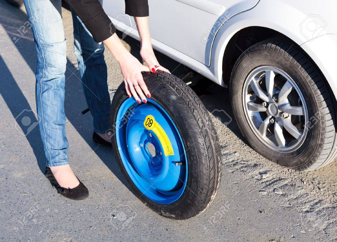 Woman changing the wheel Stock Photo - 8025785