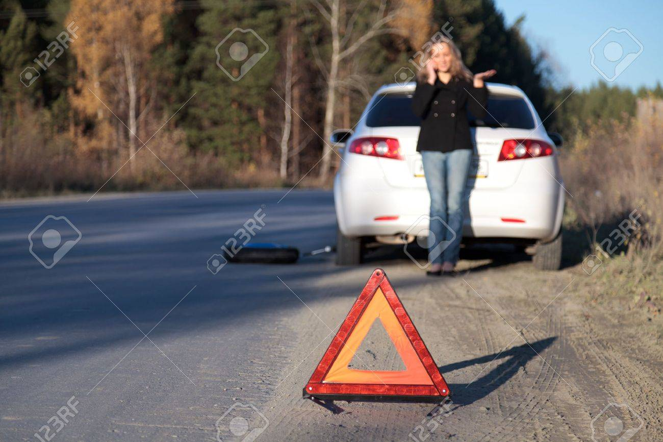 Young woman standing by her damaged car and calling for help. Focus is on the red triangle sign. Shallow depth of view Stock Photo - 8025776