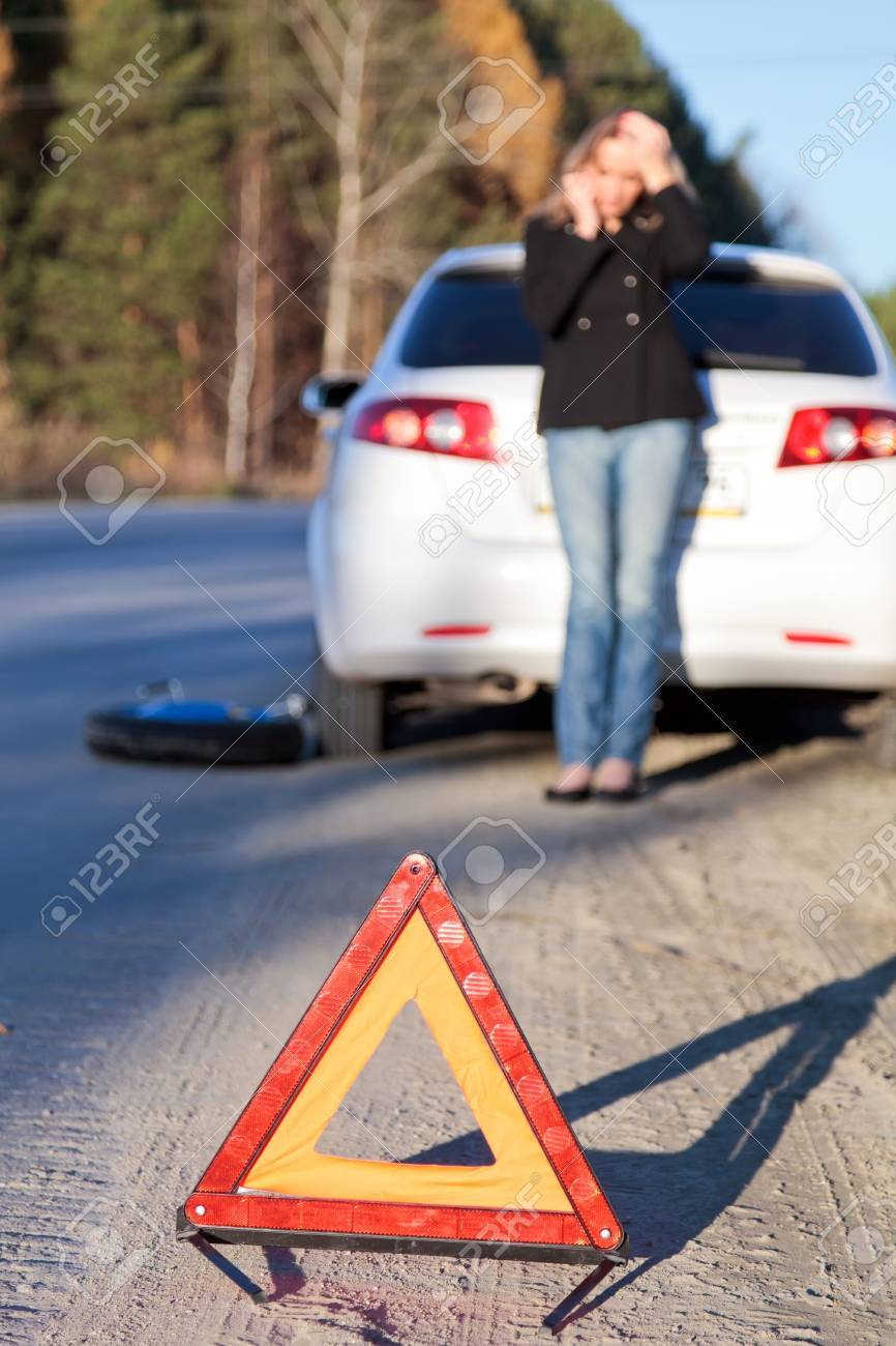 Young woman standing by her damaged car and calling for help. Focus is on the red triangle sign. Stock Photo - 8025782