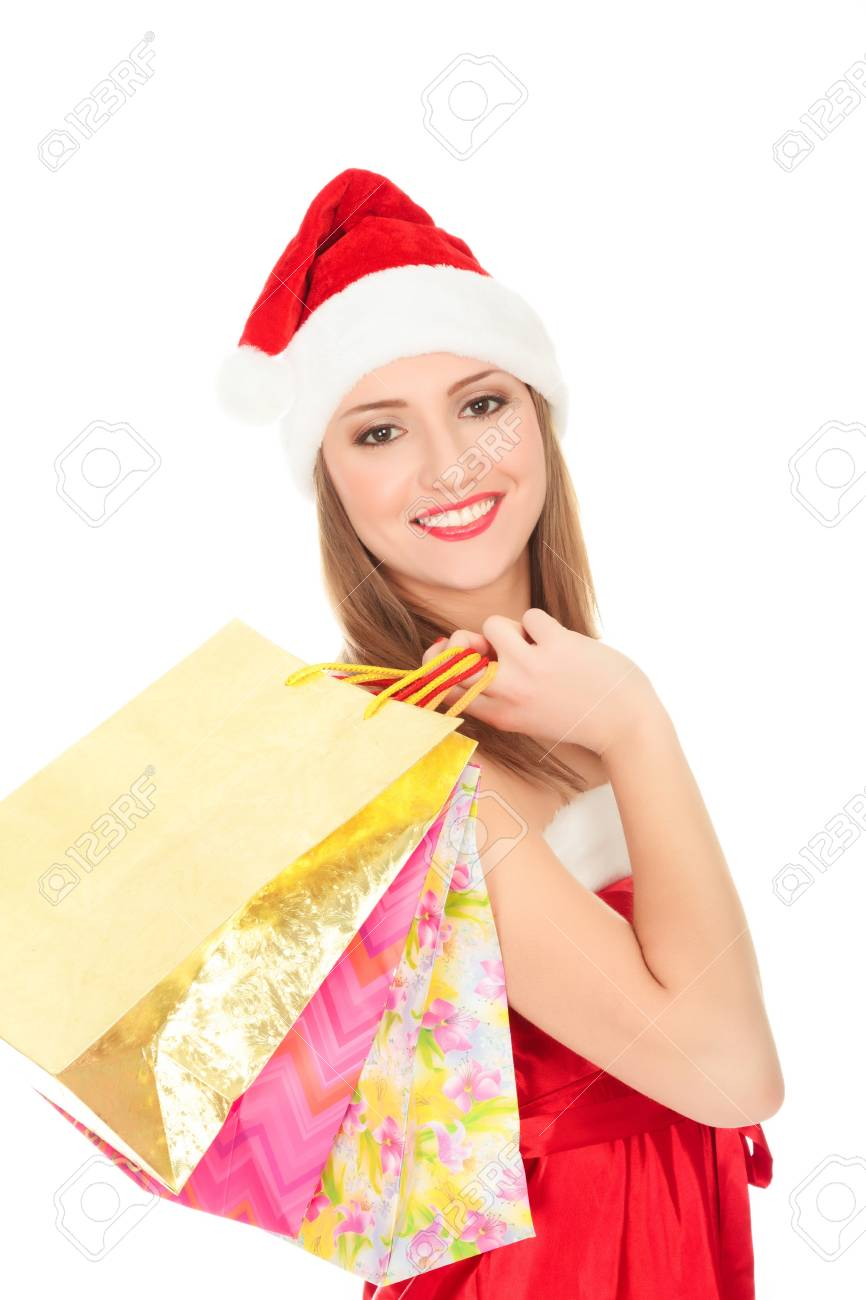 Pretty girl in a red Christmas hat with colorful bags isolated over white background. Stock Photo - 8366976