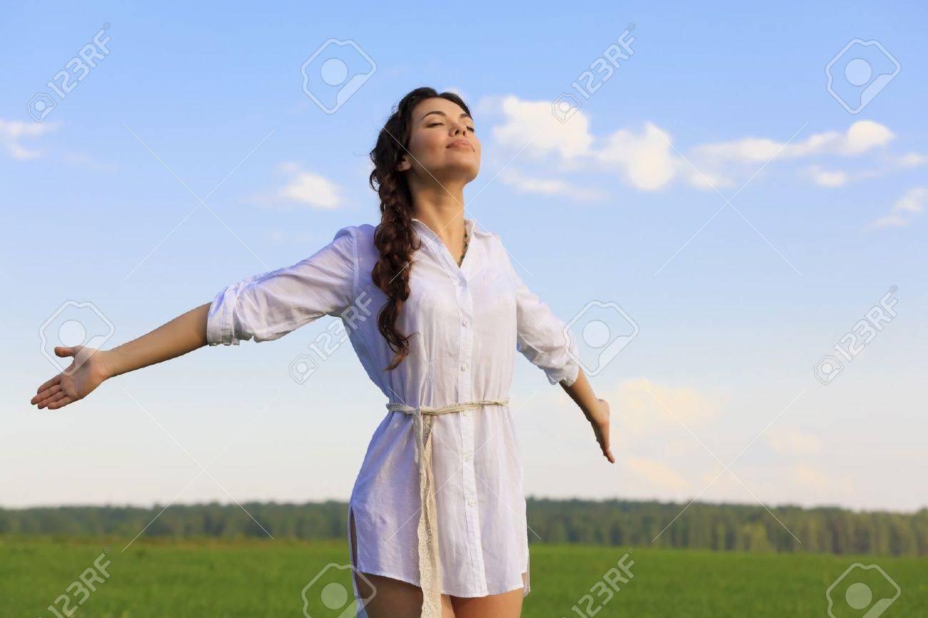 Young happy woman in green field Stock Photo - 10075500