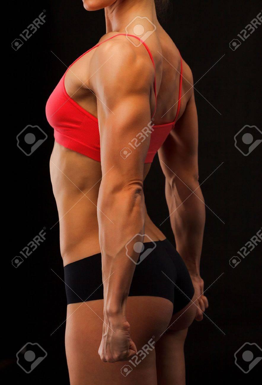 Female fitness bodybuilder posing against black background Stock Photo - 12498951