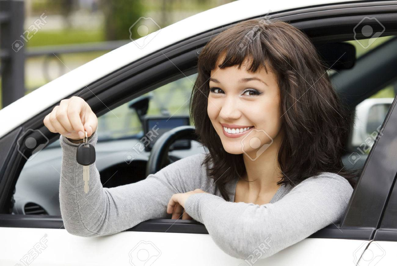 Pretty female driver in a white car showing the car key - 38834460
