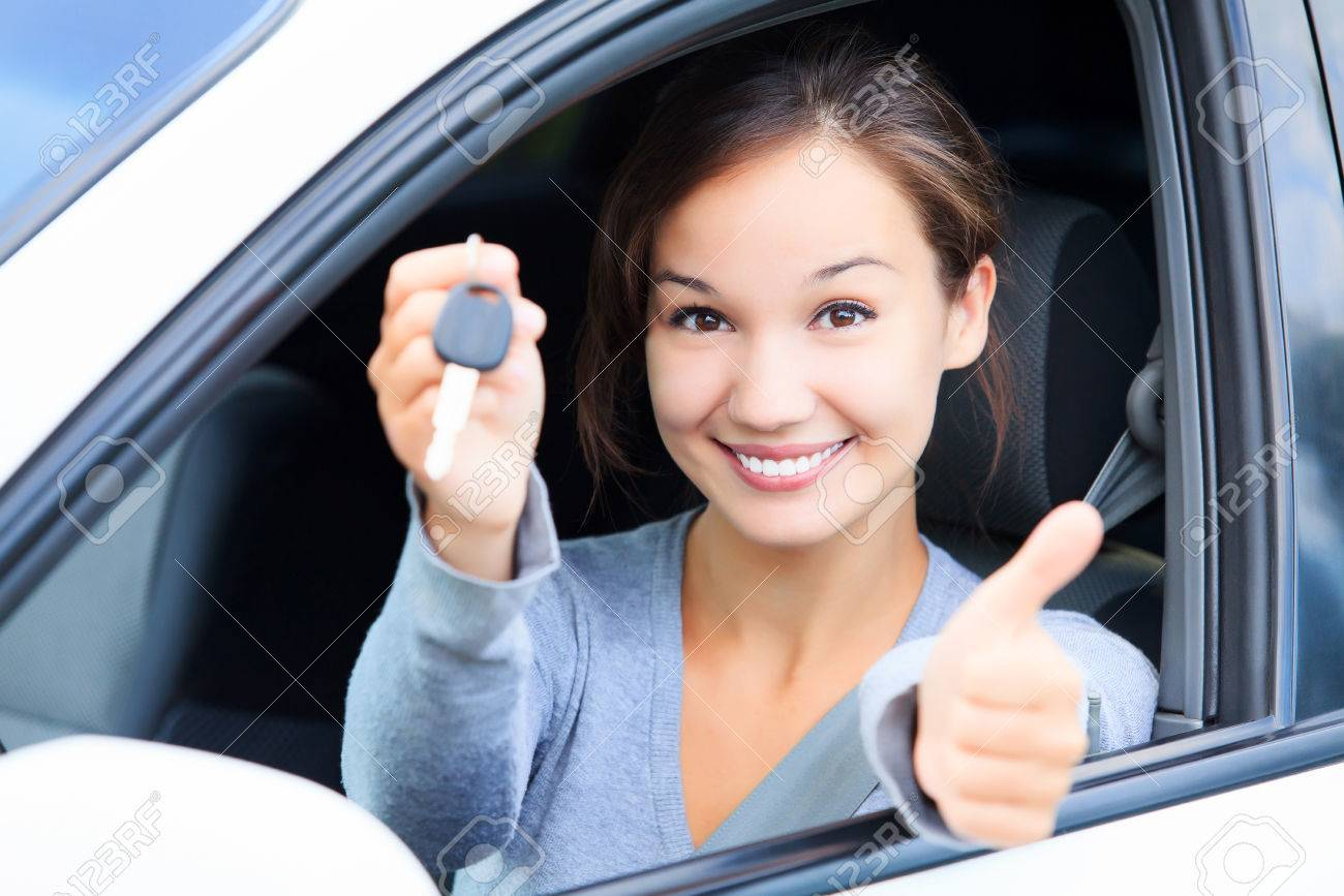 Happy girl in a car showing a key and thumb up gesture - 39545719