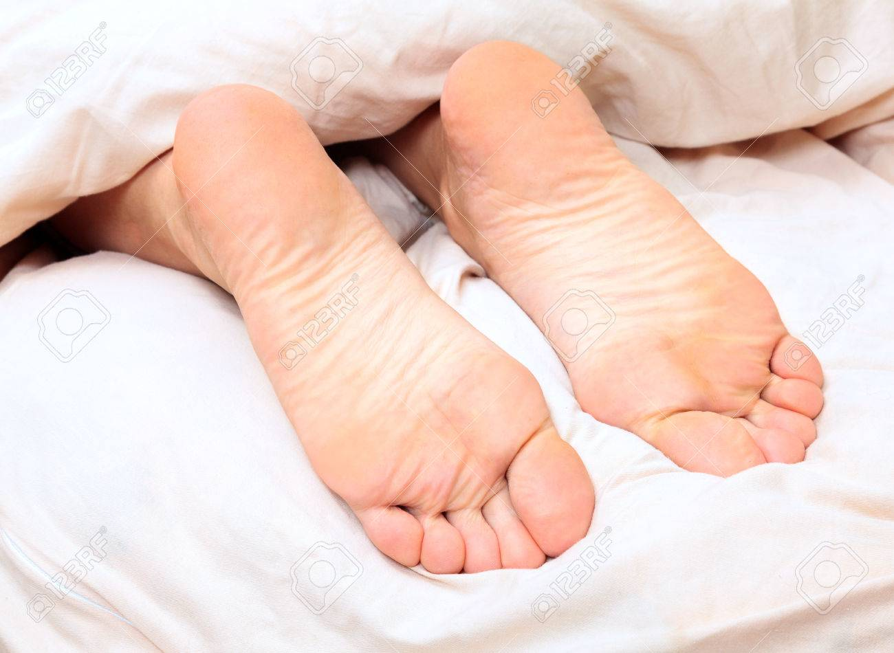 female bare feet under the blanket stock photo, picture and royalty