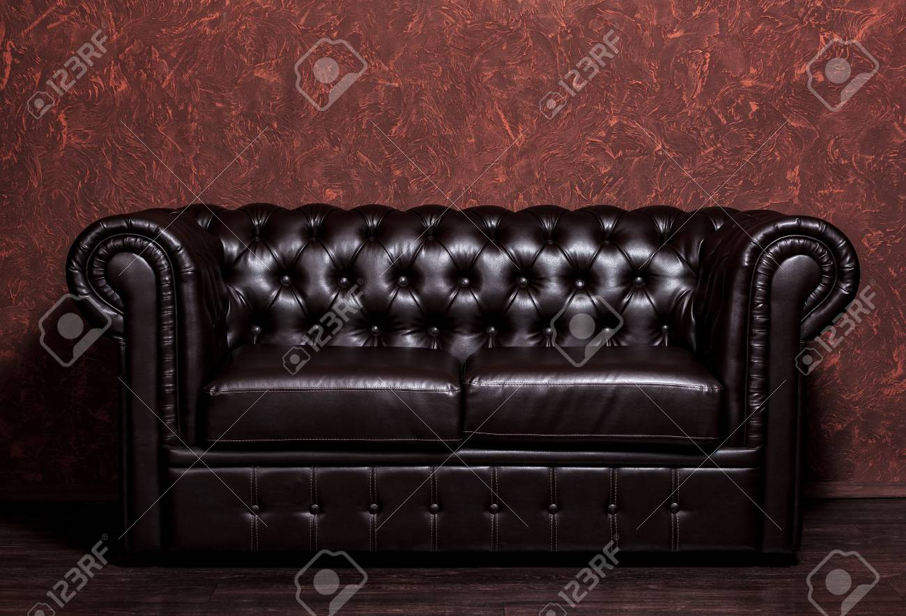 Vintage old dark brown leather sofa with grunge brown wall in..
