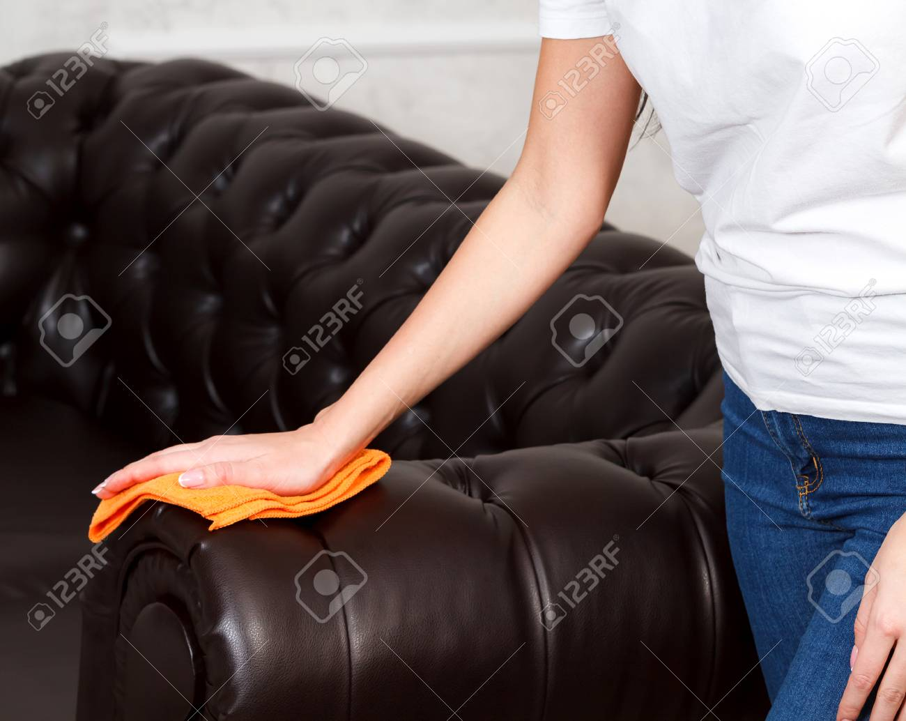 shot of female hand wiping brown leather chester couch or sofa - 97194599