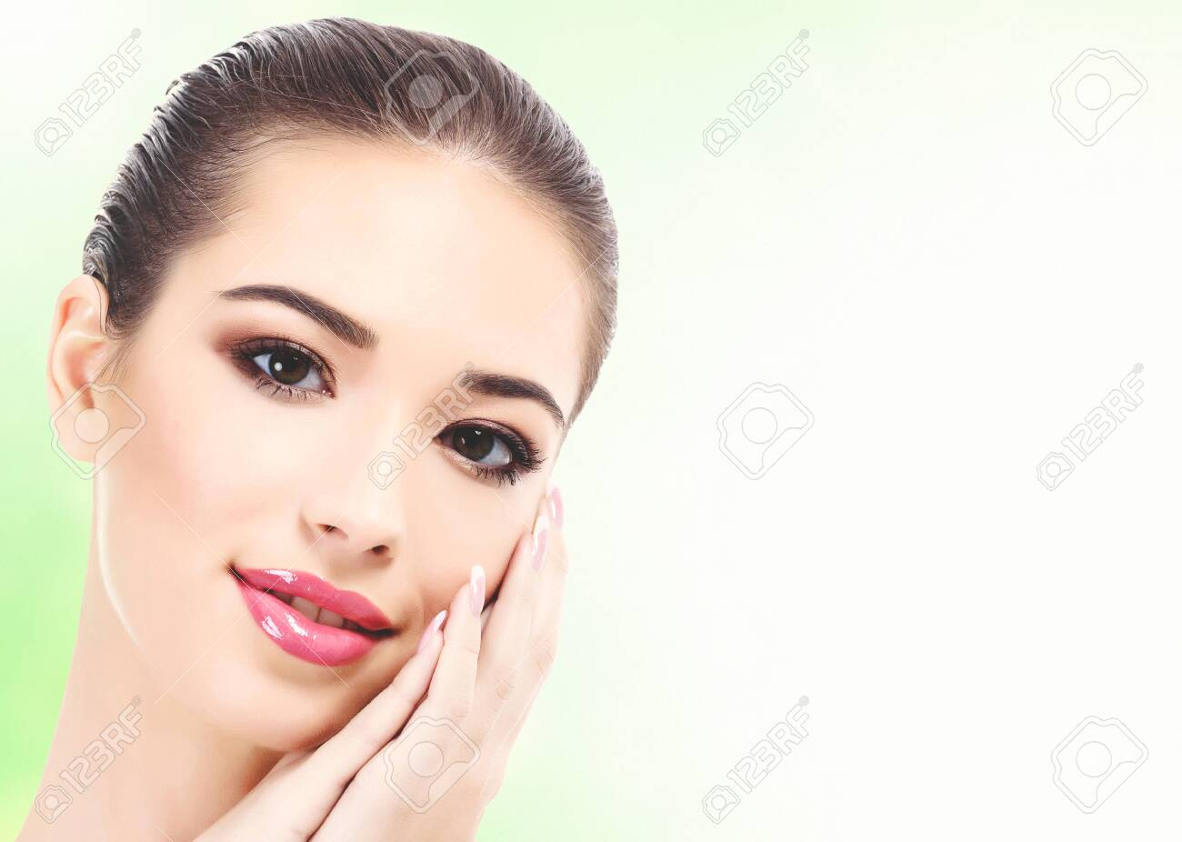 Closeup shot of beautiful woman with clean fresh skin, abstract green blurred background with copyspace - 121768134