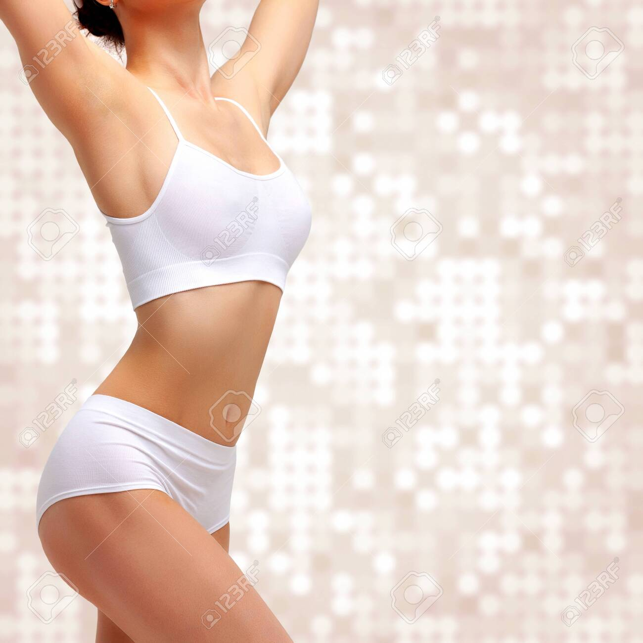 Slim slender woman in white underwear posing against abstract background. Wellness and body care concept. Healthy lifestyle - 129952187