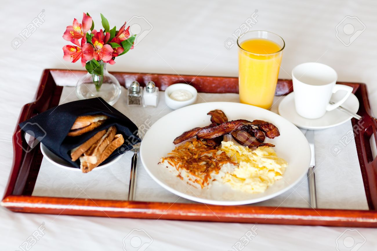 delicious breakfast served on the tray on the hotel room bed stock