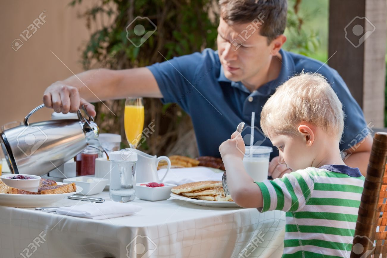 family of two eating nicely served breakfast outside; handsome young man pouring some coffee and his cute son eating delicious pancakes at breakfast time Stock Photo - 20680308