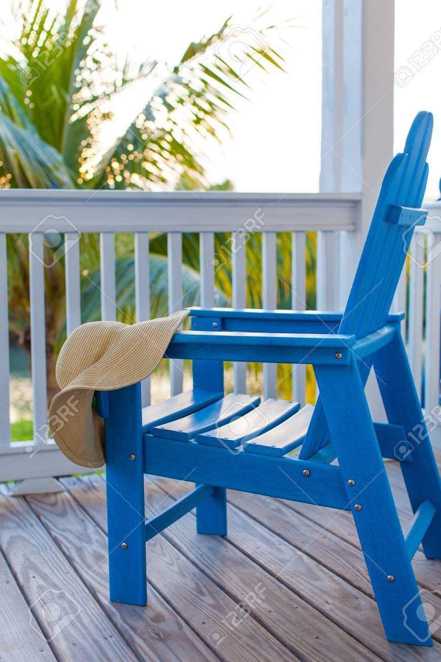 Blue Empty Adirondack Chair With Sunhat On It At The Balcony