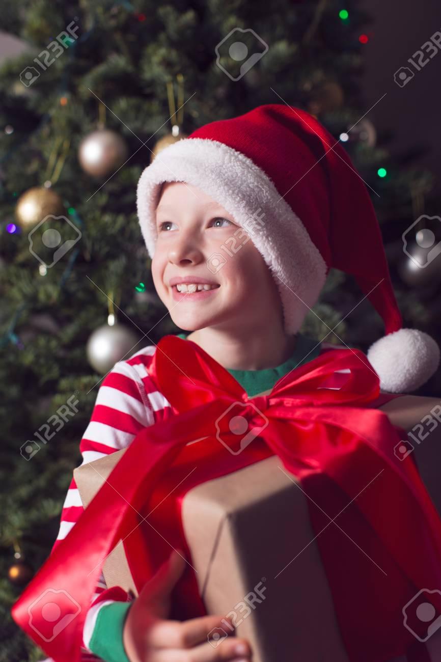 Glücklicher Junge In Elf Mütze Hält Große Weihnachtsgeschenk Für Ein ...
